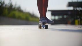 Het meisje berijdt een skateboard voorbij de camera, in het kader van de benen in tennisschoenen stock video