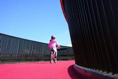 Het meisje berijdt fiets op roze cycleway in Auckland Stock Fotografie