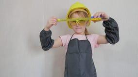 Het meisje in beschermende helm en beschermende brillen, denkt over het project Kinderjaren, bouw, architectuur, de bouw stock videobeelden