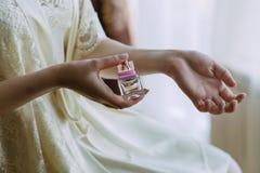 Het meisje bestrooit zich met parfum royalty-vrije stock afbeeldingen