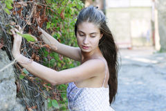 Het meisje bevindt zich dichtbij de muur Royalty-vrije Stock Foto