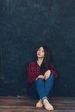 Het meisje bevindt zich dichtbij de muur in de Studio Royalty-vrije Stock Foto's