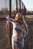 Het meisje bevindt zich dichtbij het ijzernet bij zonsondergang in een grijze blouse en borrels Stock Fotografie