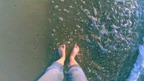 Het meisje bevindt zich dichtbij het overzees en de golven rollen haar op haar voeten stock video