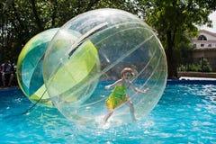 Het meisje bevindt zich in een ballon die op water in stadspark drijven in Volgograd Stock Fotografie