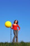 Het meisje bevindt zich en blaast met de ballon van de voetpomp op Stock Foto's