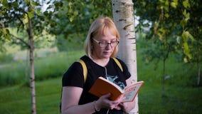 Het meisje bevindt zich met een boek in haar handen onder een boom en bekijkt de pagina's Zij kijkt zeer nadenkend stock videobeelden