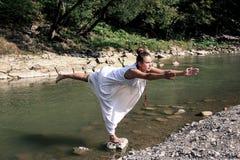 Het meisje bevindt zich op één been en doet yogaoefeningen, stock foto's