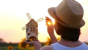Het meisje bevindt zich op een gebied van zonnebloem en houdt een stuk speelgoed windmolen in haar handen De molen roteert in de  stock video