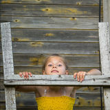 Het meisje bevindt zich op een houten ladder bij de muur van een dorpshuis Stock Fotografie