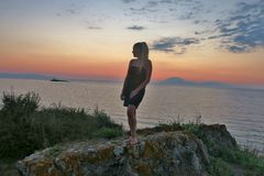 Het meisje bevindt zich op een rots en bekijkt de mooie mening van het overzees en de zonsondergang royalty-vrije stock fotografie