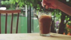 Het meisje beweegt bevroren koffie Koude drank op de lijst stock videobeelden