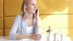 Het meisje beweegt en drinkt thee en spreekt telefonisch in koffie stock footage
