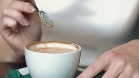 Het meisje beweegt koffie met een lepel terwijl in een koffie, de dalingen van de dalingskoffie in een mok, close-up, langzame mo stock video