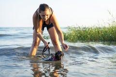 Het meisje is bezet met haar hond die, voor de ontwikkeling van de spieren van de rug zwemmen stock foto