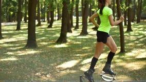 Het meisje is bezig geweest met geschiktheid in de bosbus voor Kangoo-Sprong Een populair soort aerobics stock videobeelden
