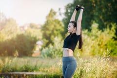 Het meisje is bezig geweest met gymnastiek in stadspark Geschiktheid in aard Ochtendoefening met een mooie, atletische vrouw stock foto's