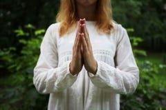 Het meisje bidt met haar handen Stock Fotografie