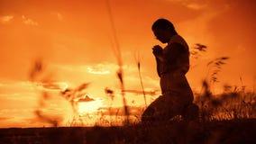 Het meisje bidt het meisje vouwde haar indient gebedsilhouet bij zonsondergang langzame geanimeerde video Het meisje vouwde haar  stock footage