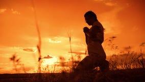 Het meisje bidt het meisje vouwde haar indient gebedsilhouet bij zonsondergang langzame geanimeerde video Het meisje vouwde haar  stock video