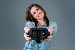 Het meisje biedt aan om glazen virtuele werkelijkheid, VR-beschermende brillen, VR-Hoofdtelefoon glazen te dragen Stock Foto