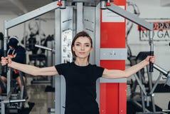Het meisje bij de gymnastiek op een simulator Stock Foto