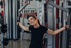 Het meisje bij de gymnastiek op een simulator Stock Afbeelding