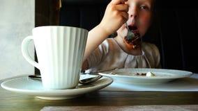 Het meisje bij de lijst heeft een cake van de vorkchocolade stock footage