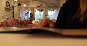 Het meisje bij de lijst in de koffie volgt het menu met haar vinger stock footage