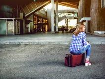 Het meisje bij de luchthaven zit op een koffer wachtend op vliegtuigfli Royalty-vrije Stock Foto