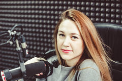 Het meisje bij de microfoon in de Studio Royalty-vrije Stock Afbeeldingen