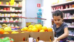 Het meisje bij de opslagmarkt kiest fruitsinaasappel stock footage