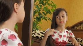 Het meisje bij de spiegel met geschilderde lippen Het meisje kamt haar haar Het kind bij de spiegel stock videobeelden