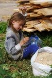 Het meisje bij de zaagmolen verzamelt zaagsel royalty-vrije stock foto