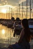 Het meisje bij de zonsondergang bekijkt de pijler royalty-vrije stock fotografie