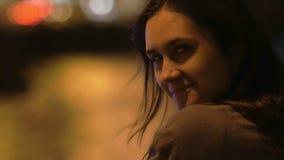 Het meisje bij nacht kijkt weg in camera, glimlachen, draaien De wind blaast haar haar, vage lichten, sideview, close-up, langzam stock video