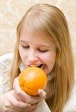 Het meisje bijt een sinaasappel stock afbeelding