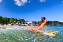 Het meisje in bikini heeft een pret op brandingsraad Stock Afbeeldingen