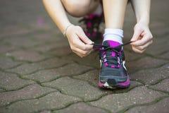 het meisje bindt de schoen van kantsporten alvorens te lopen stock foto