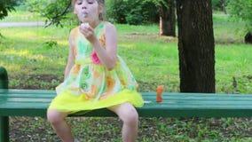 Het meisje blaast bellen op bank en loopt het in groen park de achterstand in bij de zomer stock footage