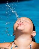 Het meisje blaast een waterspuiten terwijl het zwemmen Stock Foto