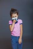 Het meisje blaast haar gerimpelde neus en een zakdoek stock foto's