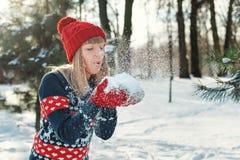 Het meisje blaast sneeuw met vuisthandschoenen en maakt een wens stock fotografie