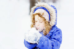 Het meisje blaast sneeuw met vuisthandschoenen, op sneeuwvlokken bokeh backg Stock Foto