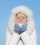 Het meisje blaast sneeuwvlokken van de hand weg Royalty-vrije Stock Afbeeldingen