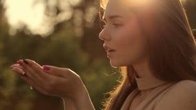 Het meisje blaast stofgoud van haar handen stock videobeelden