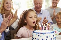 Het meisje blaast uit de Kaarsen van de Verjaardagscake bij Familiepartij royalty-vrije stock fotografie