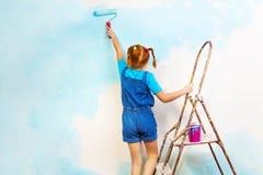 Het meisje in blauw schildert de muur op een ladder stock foto