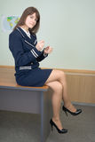 Het meisje in blauwe kleren zit op een lijst op kantoor royalty-vrije stock afbeelding