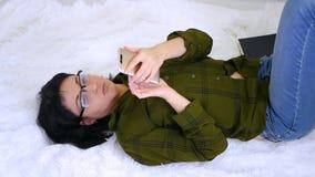 Het meisje blogger ligt op het bed en raakt het scherm die van haar smartphone, aan Internet thuis werken informatie stock video